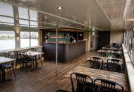 Salon met bar en tafels en stoelen in hotelschip
