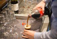 Glas cola wordt ingeschonken aan bar