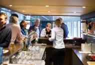 Mensen bestellen drinken aan de bar van Hotelschip It Beaken