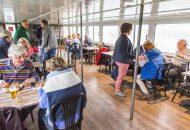 Salon met mensen di zitten te eten in Hotelschip It Beaken