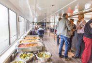 Mensen staan gezellig te praten, eten en drinken op Hotelschip It Beaken