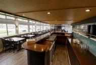 Salon met bar, tafels en stoelen van hotelschip in Heeg