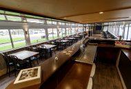 Salon van hotelschip met bar en tafels en stoelen